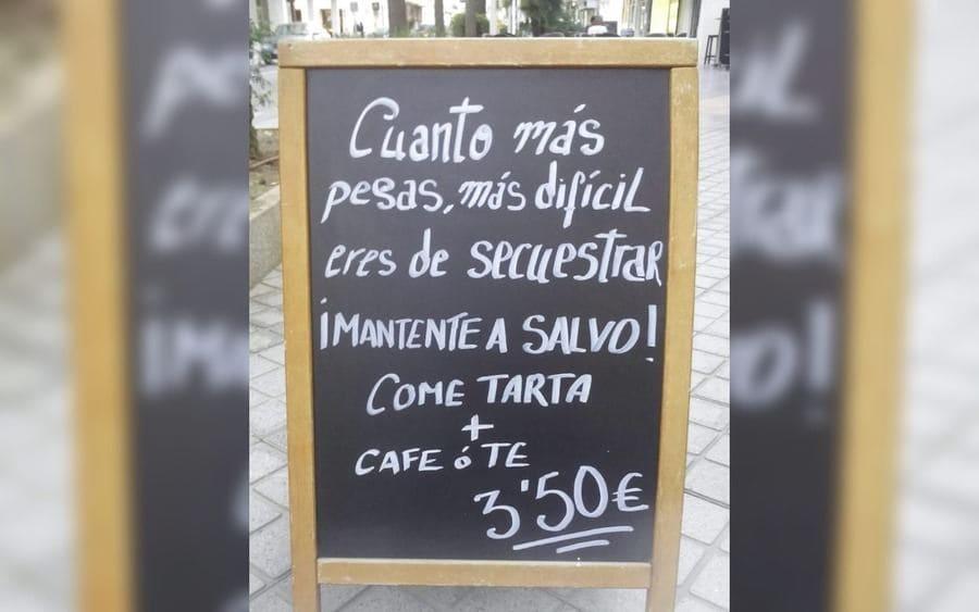Letrero que lee: Cuanto más pesas, más difícil eres de secuestrar ¡Mantente a Salvo! Come tarta + Café o té 3,50 Euros