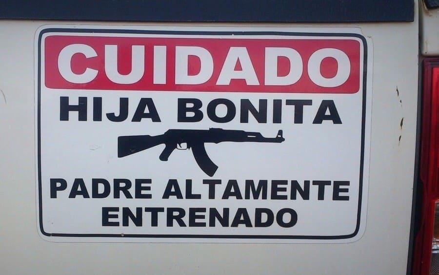 Letrero que lee: Cuidado, hija bonita, seguido de una imagen de una escopeta y termina: padre altamente entrenado