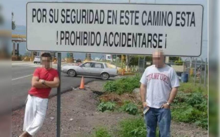 Dos tipos rudos posan junto a un letrero que lee: Por su seguridad, en este camino está ¡prohibido accidentarse!