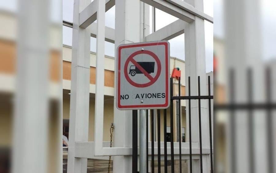 Letrero con señal de prohibidos camiones que lee: prohibido aviones