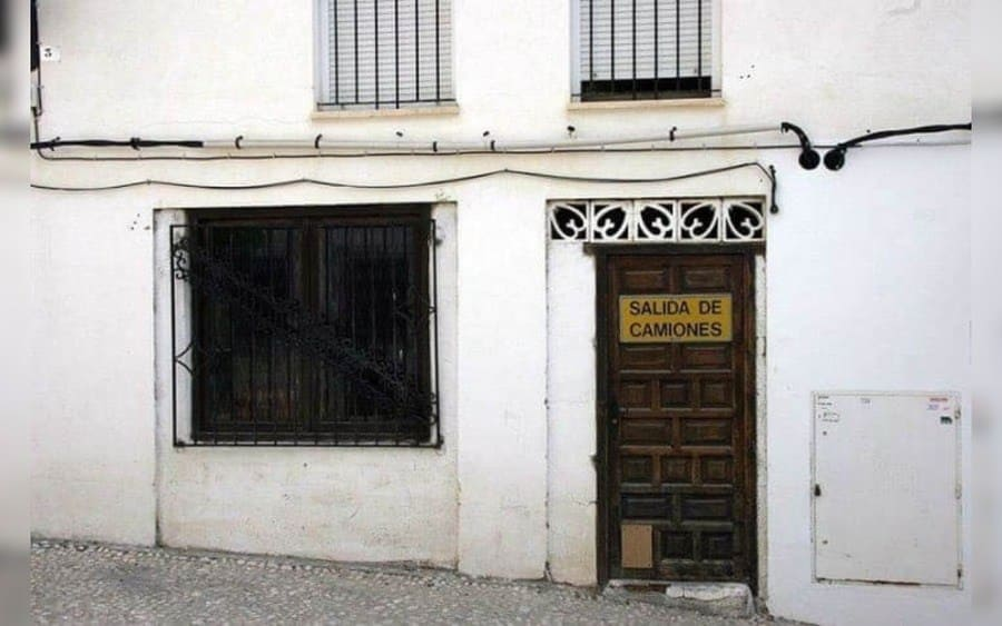 Letrero colocado sobre una puerta pequeña, que lee: Salida de camiones