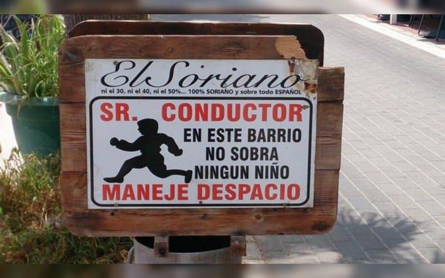 Letrero que lee: El Soriano…Señor conductor, en este barrio no sobra ningún niño, maneje despacio