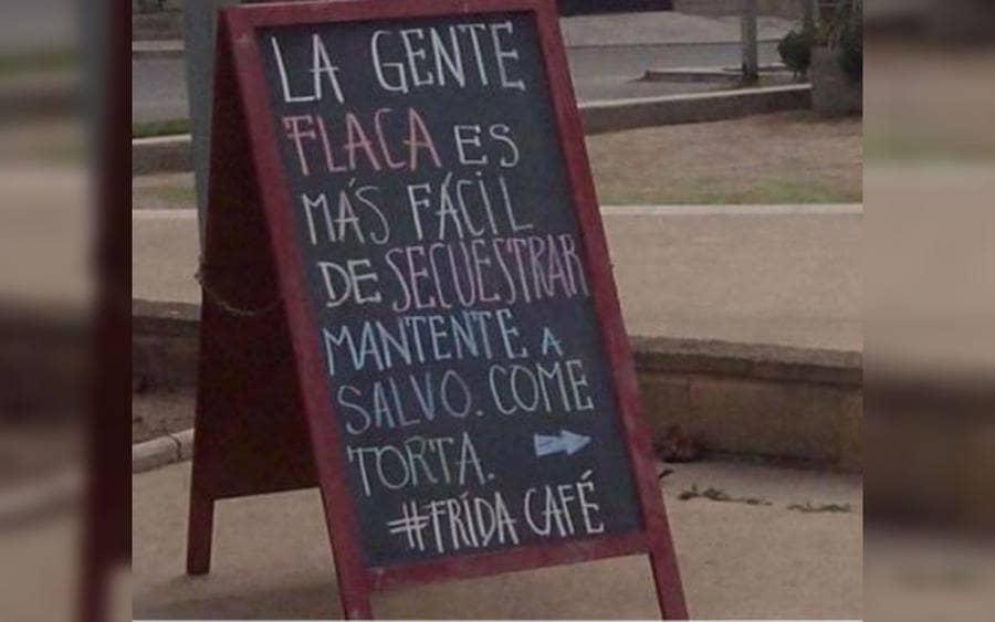 Letrero que lee: La gente flaca es más fácil de secuestrar. Mantente a salvo, come torta. Frida Café