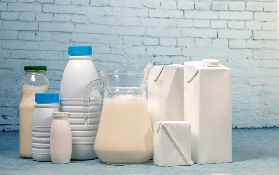 Mix of milk bottles and package isolated on a blue brick background