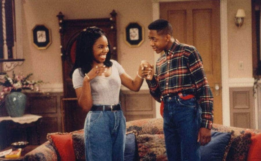 Jaleel White holding Kellie Shanygne Williams' hand in the living room in a scene from Family Matters