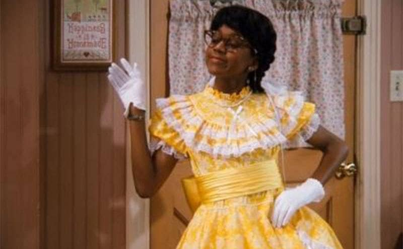 Steve Urkel dressed as Myrtle Urkel waving as he comes in the kitchen door in a scene from Family Matters