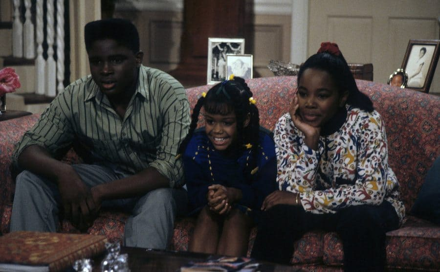 Darius McCrary, Jaimee Foxworth, and Kellie Shanygne Williams sitting on the couch watching intensely in a scene from Family Matters