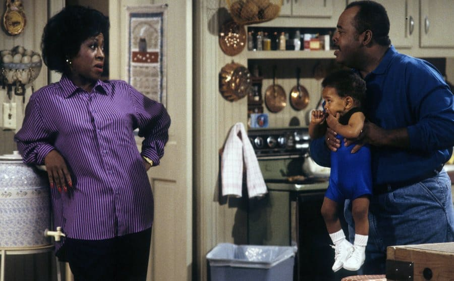 Jo Marie Payton with Reginald Vel Johnson holding Joseph or Julius Wright in the kitchen in a scene from Family Matters