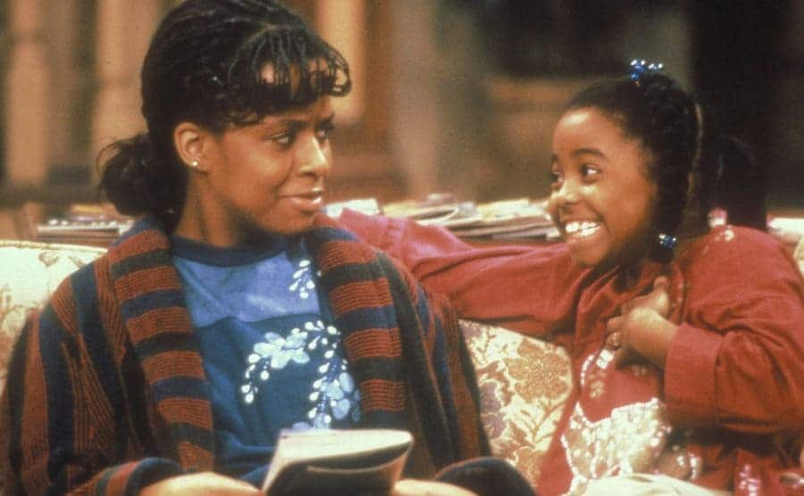 Tempsett Bledsoe and Keshia Knight Pulliam sitting on the couch in a scene from The Cosby Show