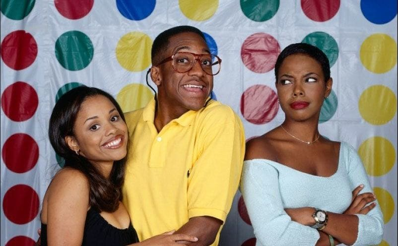 Michelle Thomas, Jaleel White, and Kellie Shanygne Williams posing together in front of a white wall with multi-colored dots