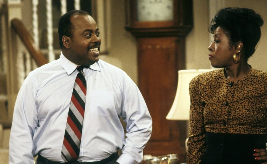 Reginald Vel Johnson and Jo Marie Payton talking to each other in the living room in a scene from Family Matters