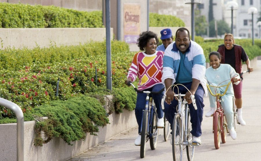 Reginald Vel Johnson, Kellie Shanygne Williams, Darius McCrary, Jo Marie Payton, and Telma Hopkins riding bicycles down the sidewalk in a publicity still for Family Matters