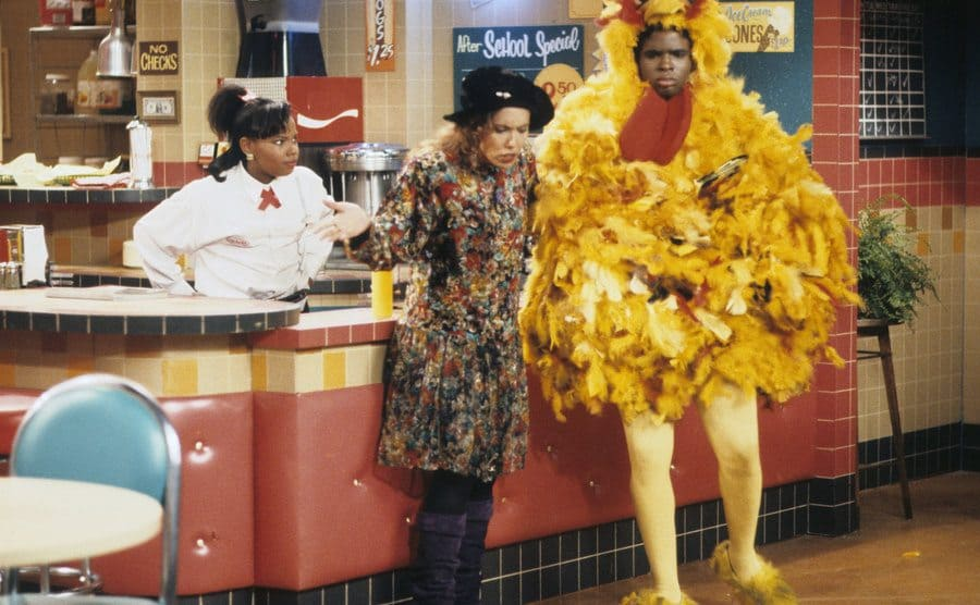Kellie Shanygne Williams, Telma Hopkins, and Darius McCrary wearing a chicken suit in a scene from Family Matters