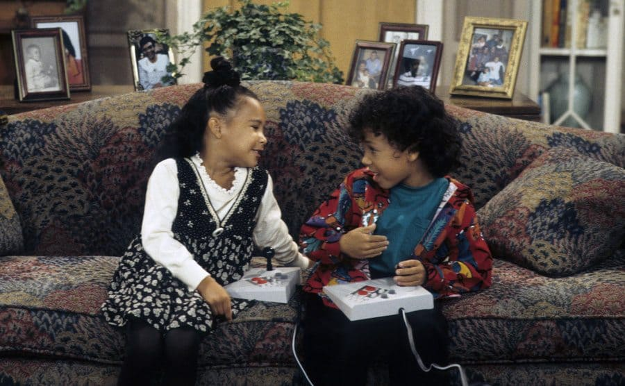 Naya Rivera and Bryton James sitting on the couch playing in a scene from Family Matters