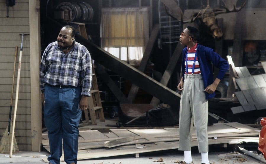 Reginald Vel Johnson upset standing with Jaleel White outside of a burned garage in a scene from Family Matters
