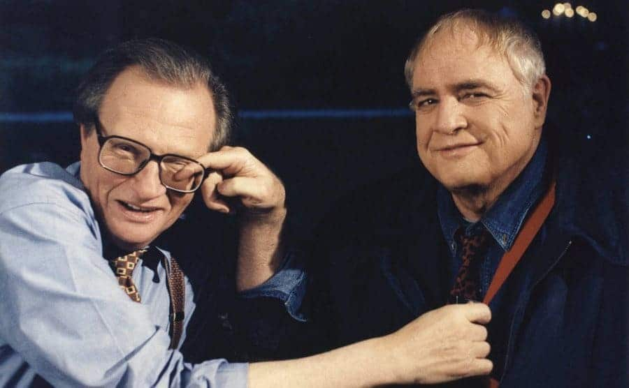 Marlon Brando touching Larry King's eye posing on the set of Larry King Live