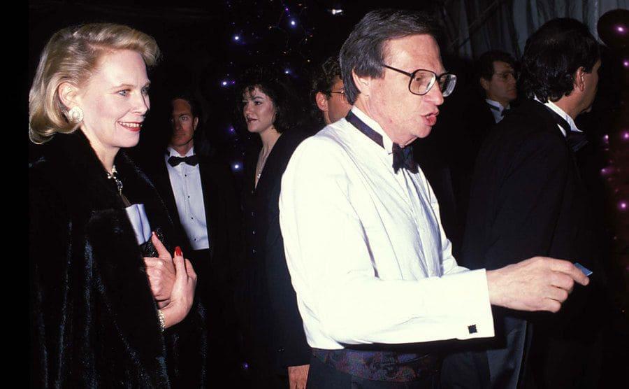 Julie Alexander walking behind Larry King on the red carpet in 1989