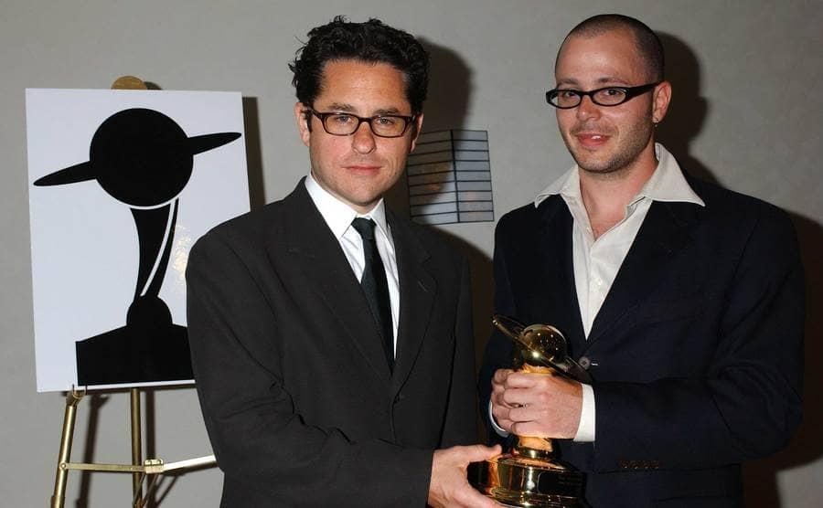 J.J. Abrams and Damon Lindelof holding their winning statue together