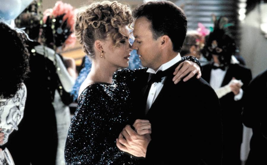 """Michelle Pfeiffer and Michael Keaton dancing at a ball dancing in a scene from the film """"Batman Returns."""""""