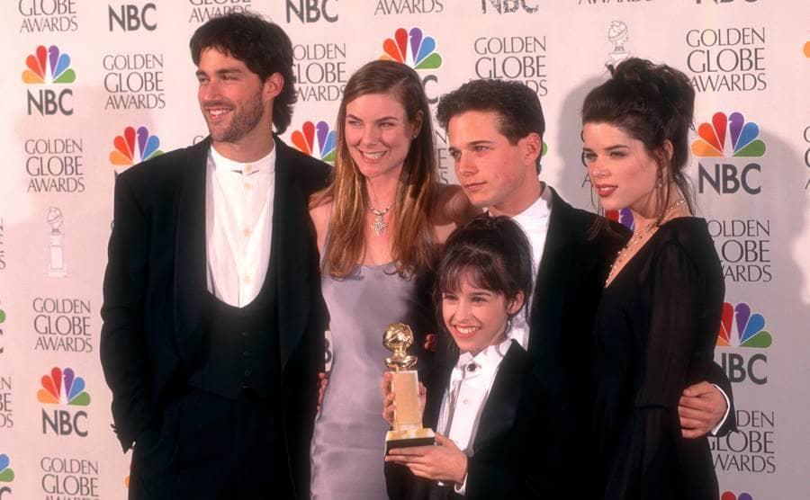 """Matthew Fox and the cast of """"Party of Five"""" posing on the red carpet with their Golden Globe Award"""