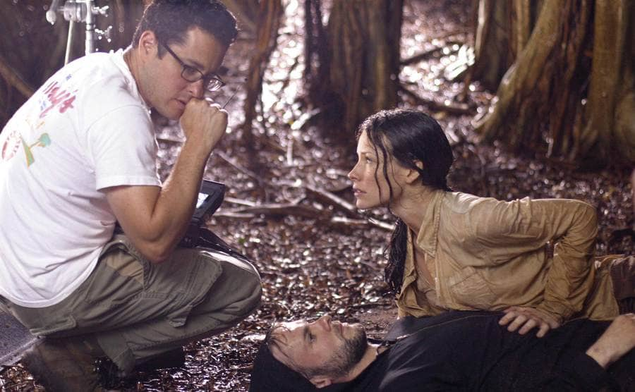 Dominic Monaghan lying on the ground with Evangeline Lilly looking over him while the director Dominic Monoghan directs the scene