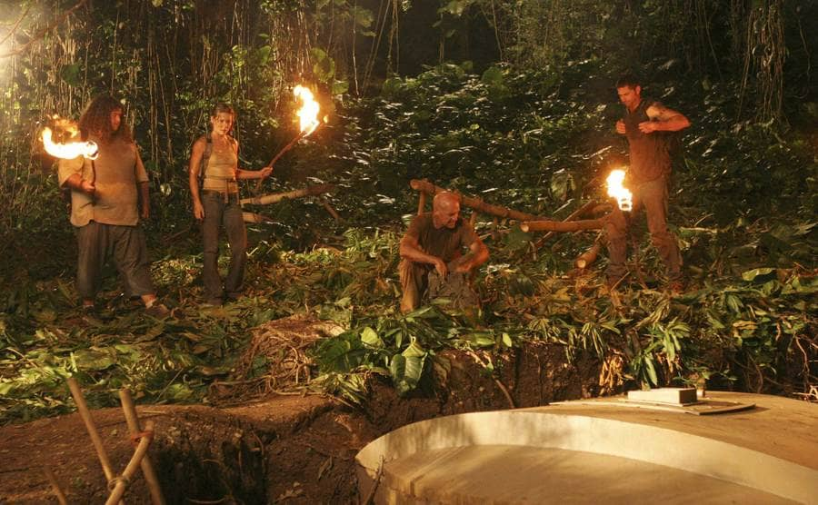 Jorje Garcia, Evangeline Lilly, Terry O'Quinn, and Mathew Fox holding torches in the woods