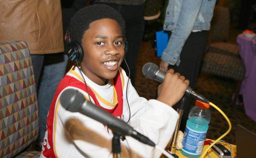 Malcolm David Kelley holding a microphone while smiling