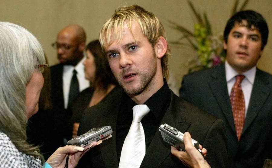 Dominic Monaghan being interviewed in a black tux and white tie