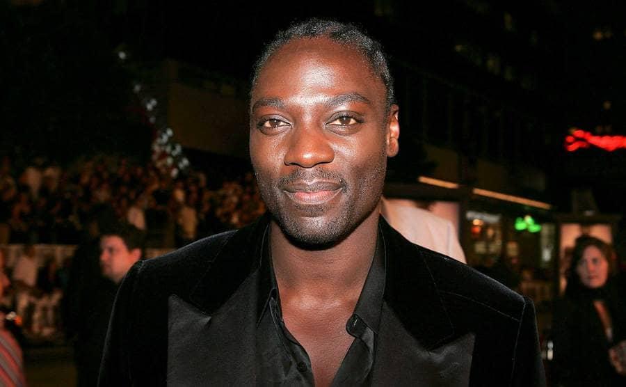 A close up of Adewale Akinnuoye-Agbaje wearing a tuxedo.