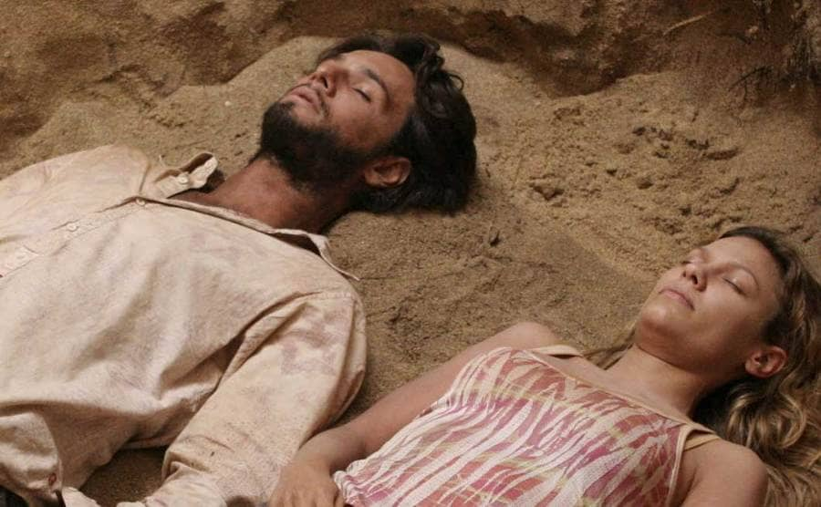 The characters Nikki and Paulo lying on the sand with their eyes closed.