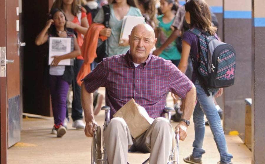 Terry O'Quinn as John Locke driving his wheelchair down a hallway at school