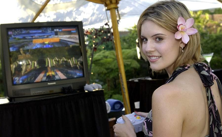 Maggie Grace with a flower in her hair playing a video game