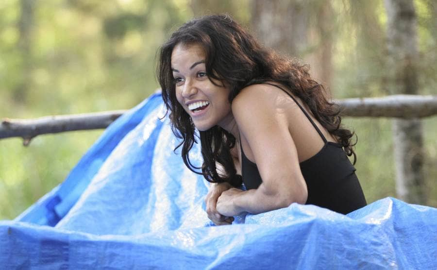 Michelle Rodriguez smiling while leaning on a blue tarp.