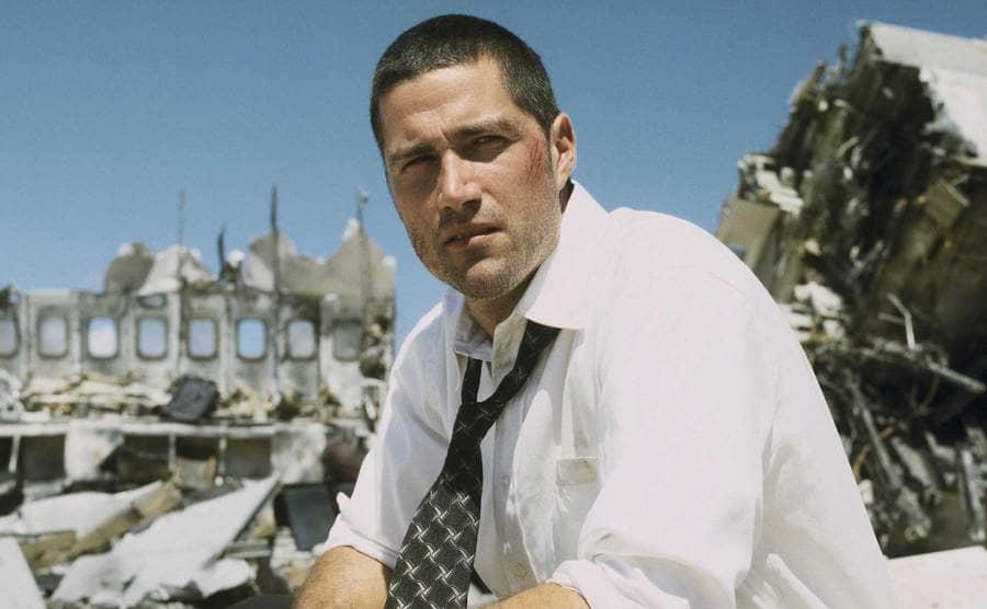 A close up of Matthew Fox sitting on a broken piece of an airplane