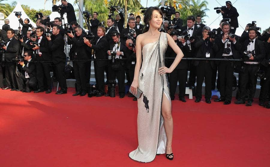 Yunjin Kim wearing a gown standing on a red carpet and with photographers lined up behind her