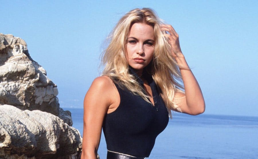Pamela Anderson posing on rocks on the shore.