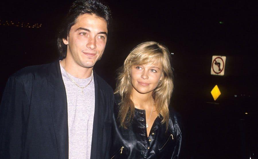 Scott Baio and Pamela Anderson holding hands walking on the sidewalk.