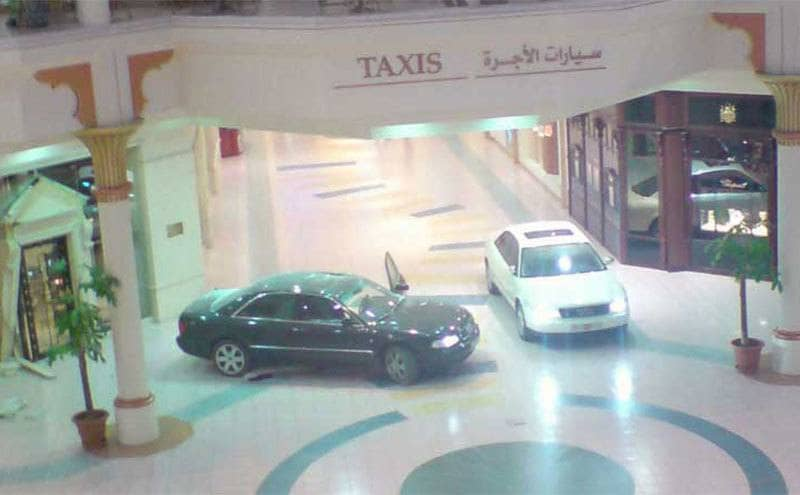 CCTV footage of a black car with its door open and a white car inside of the Wafi mall with a sign for Taxis in the background