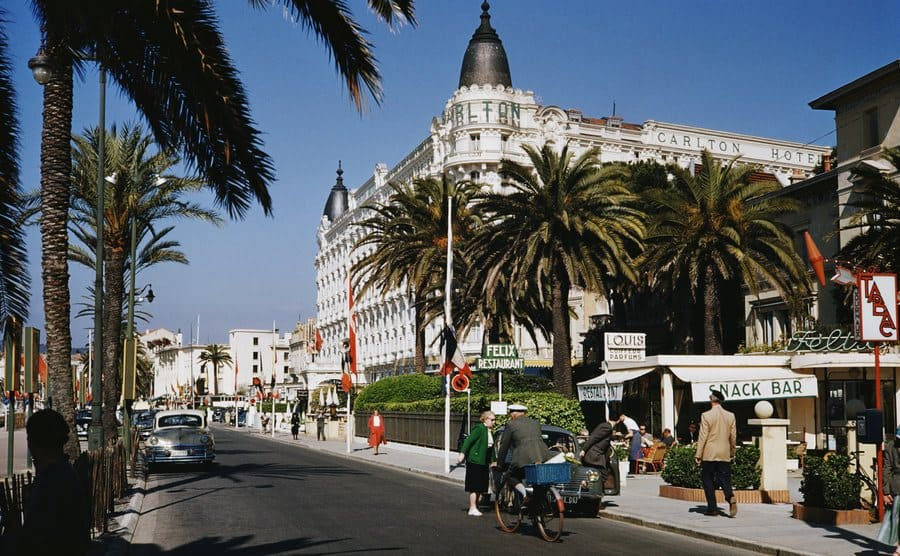 The Cannes Carlton Hotel with people biking down the street and walking on the sidewalk