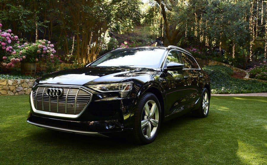 A black Audi in a grassy backyard