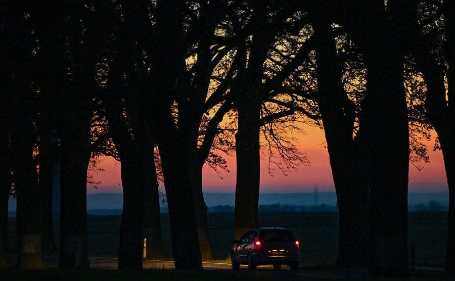 A car driving off into the sunset
