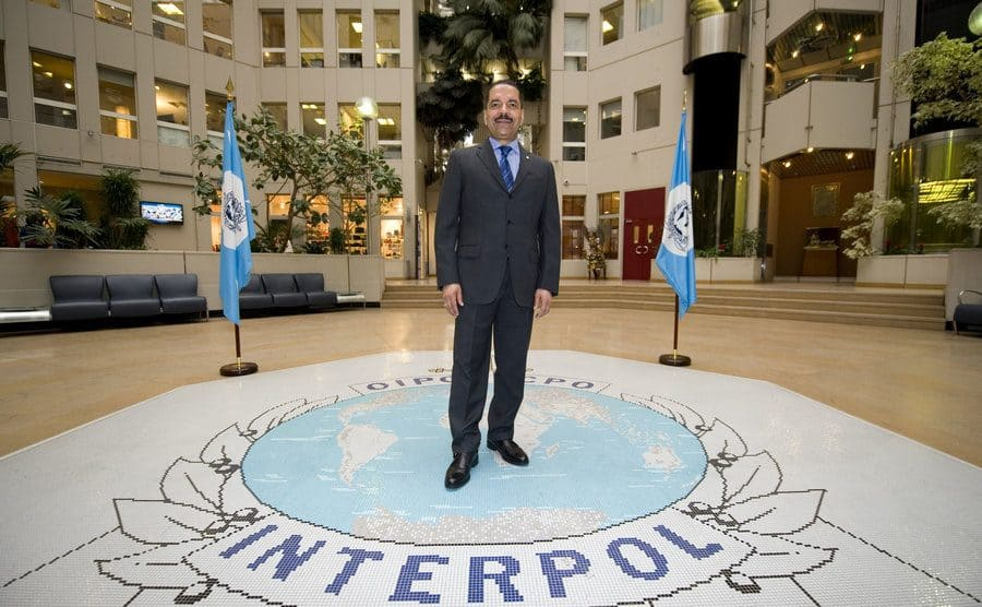 Robert Noble standing in the middle of Interpol's logo in the atrium of the agency's headquarters