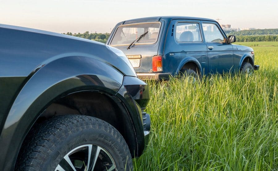 An old blue car in a grassy field with the tip of a black jeep in the photograph behind it