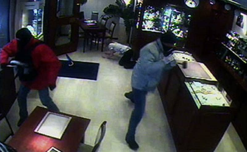 Two men robbing a jewlery store with black masks on
