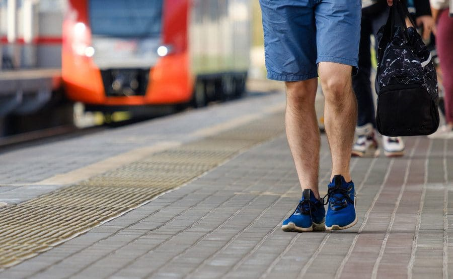 A man walking next to a railway platform with blue shorts and sneakers