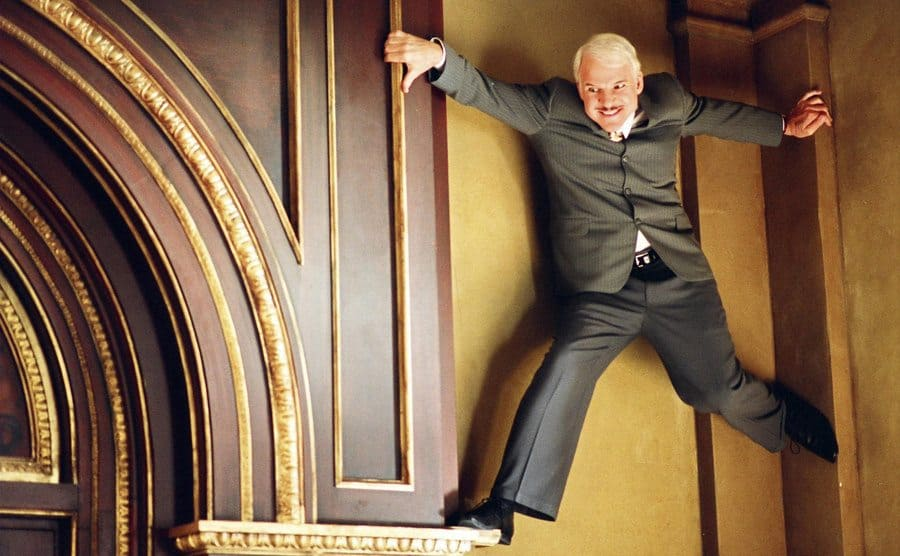 A film still of Steve Martin holding himself up on the top of a wall as hes hiding form someone