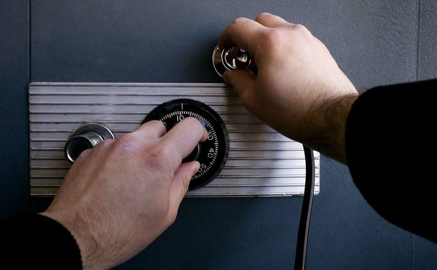 A stock image of a man using a stethoscope to try and open a safe with a numbered dial