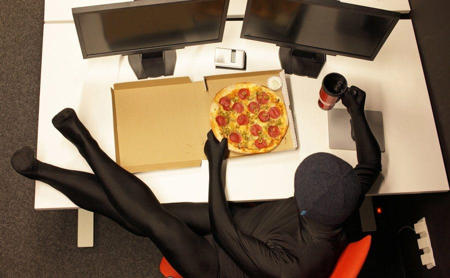 A masked hacker having a pizza and coffee at her desk with two screens on it and with her feet up
