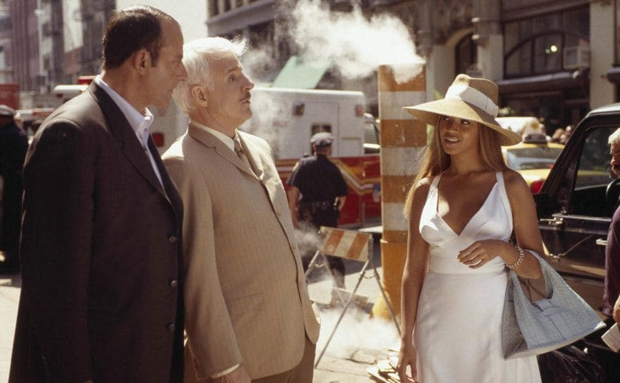 Jean Reno and Steve Martin in the street talking to Beyonce in a scene from The Pink Panther