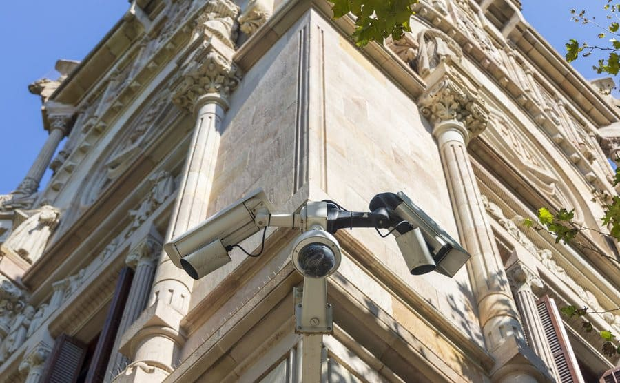 Security cameras on the outside corner of a light brick building